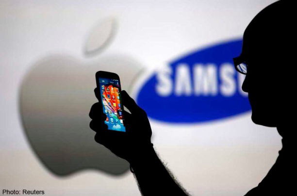 A man is silhouetted against a video screen with Apple and Samsung logos as he poses with a Samsung Galaxy S4 in this photo illustration taken in the central Bosnian town of Zenica